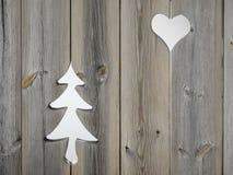 Los adornos del árbol de navidad y del corazón en obturador de madera suben Fotos de archivo libres de regalías