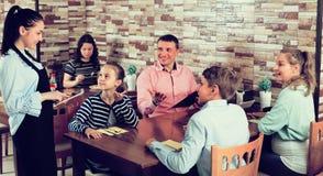 Los adultos con los niños están dando orden a la camarera alegre Fotos de archivo