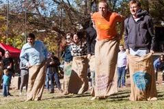 Los adultos jovenes compiten en raza de saco en el festival de Atlanta Imágenes de archivo libres de regalías