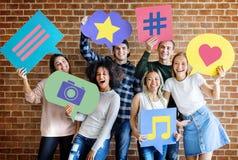 Los adultos jovenes felices que llevan a cabo pensamiento burbujean con medios concentrado social imágenes de archivo libres de regalías