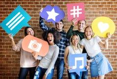 Los adultos jovenes felices que llevan a cabo pensamiento burbujean con los medios iconos sociales del concepto Fotografía de archivo