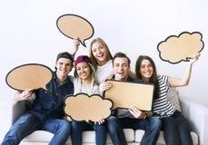 Los adultos jovenes felices que soportan el copyspace llenan de carteles burbujas del pensamiento Fotografía de archivo