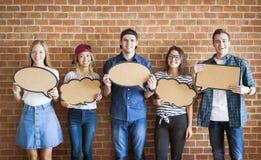 Los adultos jovenes felices que soportan el copyspace llenan de carteles burbujas del pensamiento Imagen de archivo libre de regalías