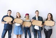 Los adultos jovenes felices que soportan el copyspace llenan de carteles burbujas del pensamiento Fotos de archivo libres de regalías