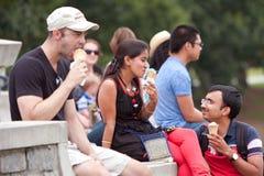 Los adultos jovenes gozan el comer de conos de helado en el festival del verano Fotos de archivo libres de regalías