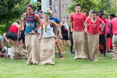 Los adultos jovenes participan en raza de saco en el día de maniobras de Atlanta fotografía de archivo libre de regalías