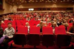 Los adultos y los niños se sientan en sillas rojas Imágenes de archivo libres de regalías