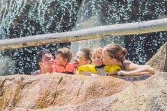 Los adultos y los niños felices en un agua parquean Imagen de archivo libre de regalías
