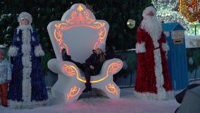 Los adultos y los niños fotografiaron sentarse en el trono cerca del árbol del Año Nuevo de la ciudad almacen de video