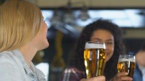 Los aficionados deportivos que tintinean la cerveza en la barra, animando para la victoria del equipo nacional, se relajan almacen de metraje de vídeo