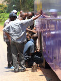 Los africanos cambian un neumático público del autobús Imágenes de archivo libres de regalías