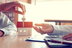 Los agentes caseros del vendedor proporcionan llave a los nuevos dueños de la casa y compradores g imagen de archivo
