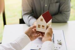 Los agentes caseros están dando los regalos de la casa a los nuevos compradores de vivienda en sitio de la oficina foto de archivo libre de regalías