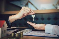 Los agentes caseros están distribuyendo llaves a los compradores de vivienda que están firmando contratos en la oficina fotos de archivo