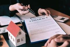 Los agentes caseros están enviando plumas a los clientes que firman un contrato para comprar un nuevo hogar imagen de archivo