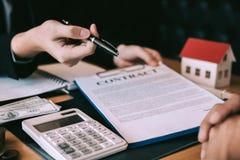 Los agentes caseros están enviando plumas a los clientes que firman un contrato para comprar un nuevo hogar imágenes de archivo libres de regalías