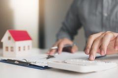 Los agentes caseros están utilizando una calculadora para calcular el período de préstamo cada mes para el cliente fotos de archivo libres de regalías