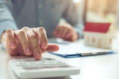 Los agentes caseros están utilizando una calculadora para calcular el período de préstamo cada mes para el cliente fotos de archivo