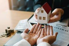 Los agentes caseros est?n dando los regalos de la casa a los nuevos compradores de vivienda en sitio de la oficina imagen de archivo libre de regalías