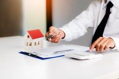 Los agentes caseros son envío dominante a los clientes que firman un contrato para comprar un nuevo hogar imagen de archivo libre de regalías
