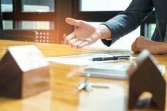 Los agentes de las ventas de casas están ofreciendo las ventas de casas, pluma se colocan en Foto de archivo