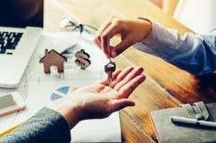 Los agentes inmobiliarios de propiedades inmobiliarias darán llaves a los arrendatarios después del contrato Foto de archivo libre de regalías