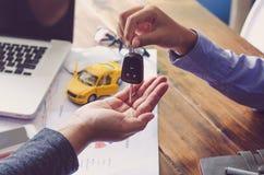 Los agentes reales del coche de la sala de exposición darán llaves a los arrendatarios imagenes de archivo