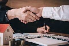 Los agentes y los compradores de ventas de casas trabajan en la firma de nuevos hogares y la sacudida de las manos imagenes de archivo