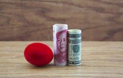 Los ahorros carmesís con moneda americana y china reflejan el ris Fotografía de archivo