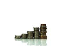 Los ahorros, las columnas cada vez mayores acuñan en el fondo blanco Fotos de archivo libres de regalías