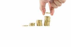 Los ahorros se cierran para arriba de la mano masculina que apila monedas de oro en el fondo blanco Imagen de archivo libre de regalías