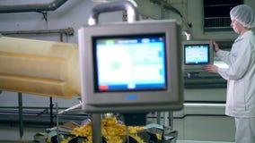 Los ajustes del mecanismo microprocesador-que produce están siendo regulados por una señora almacen de metraje de vídeo