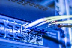 Los alambres amarillos ópticos de Internet y de la red están en los interruptores del encargado foto de archivo