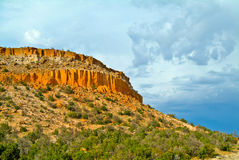 Los Alamos Ciffs in New Mexico. In late afternoon, showing red rocks and desert shrubs Stock Images