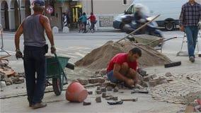Los albañiles de los constructores están reparando el camino El constructor pone la piedra de pavimentación metrajes