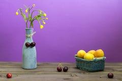 Los albaricoques están en una cesta de mimbre Las cerezas están en una tabla de madera Florero con los wildflowers en un fondo pú fotos de archivo
