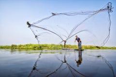 Los aldeanos están echando pescados Pescador Fishing Nets Red de pesca que lanza durante la mañana en un barco de madera, Tailand fotos de archivo libres de regalías