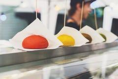 Los alimentos de preparación rápida de la calle, los bollos coloreados de la hamburguesa reman en contador Imagen de archivo