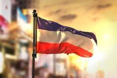 Los-altflagga mot suddig bakgrund för stad på soluppgång Backli Arkivfoton