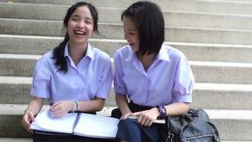 Los altos pares tailandeses asiáticos alegres lindos del estudiante de las colegialas en uniforme escolar se sientan en la escale almacen de video