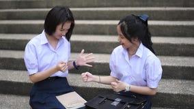 Los altos pares tailandeses asiáticos lindos del estudiante de las colegialas en uniforme escolar se están divirtiendo que juega  almacen de video