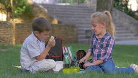 Los alumnos charlan durante almuerzo de la hendidura con los bocadillos en las manos que se sientan en hierba en patio metrajes