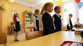 Los alumnos, colocándose cerca de los escritorios, están saludando al profesor al principio de la lección almacen de metraje de vídeo