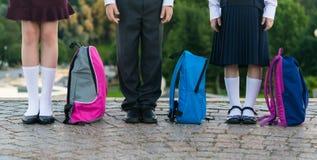 Los alumnos con las mochilas se colocan en el parque listo para ir a la escuela Fotos de archivo