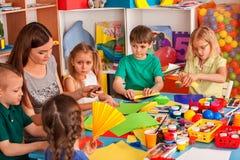 Los alumnos con las tijeras en niños dan el papel del corte imágenes de archivo libres de regalías