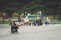 Los alumnos de la escuela de arte dibujan en el parque de la ciudad en un aire abierto en honor del día del ` s de la ciudad fotografía de archivo