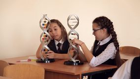 Los alumnos en uniforme escolar están estudiando la disposición de la DNA que se sienta en la sala de clase metrajes