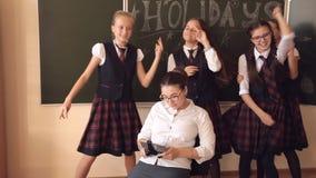 Los alumnos en uniforme escolar se están colocando cerca de un profesor que se esté sentando en una silla que juega a juegos en e almacen de metraje de vídeo