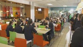 Los alumnos en uniforme escolar se sientan en las tablas con el almuerzo almacen de video