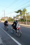 Los alumnos están montando su bici en una calle de Matsue (Japón) Foto de archivo libre de regalías